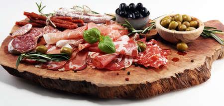Marmorschneidebrett mit Schinken, Speck, Salami und Würstchen auf Holzhintergrund. Fleischplatte Vorspeisen und Oliven