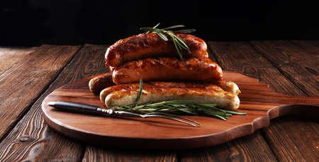Salchichas a la plancha con especias sobre una mesa de madera - Salchichas de cerdo caseras para barbacoa