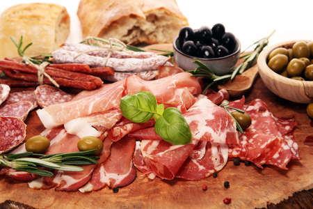Marble cutting board with prosciutto, bacon, salami and sausages on wooden background. Meat platter appetizers and olives