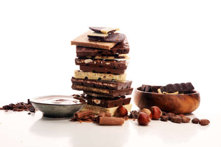 Chocolate bars on table with chocolate tower. Chocolate and nuts and choco swirl