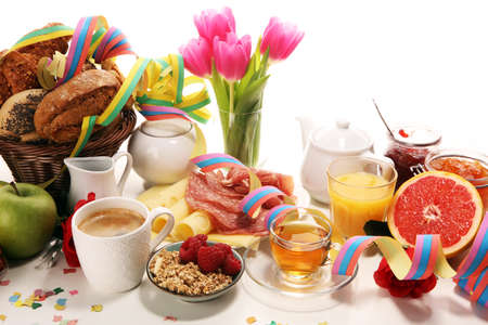 breakfast on table with bread buns, croissants, streamers, coffe and juice on carnival