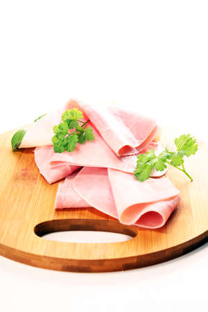Sliced ham with parsley on table. Fresh prosciutto. Pork ham sliced snack