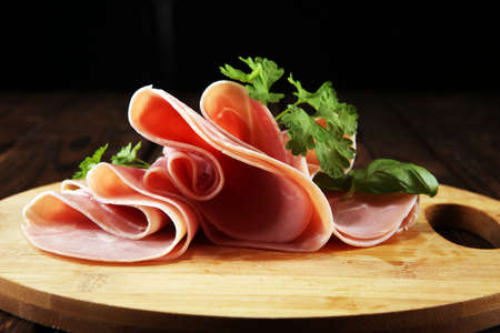 Sliced ham with parsley on table. Fresh prosciutto. Pork ham sliced snack