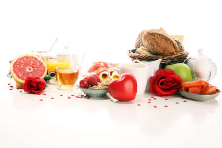 breakfast on table with bread buns, croissants, jam, coffe and juice on valentines day