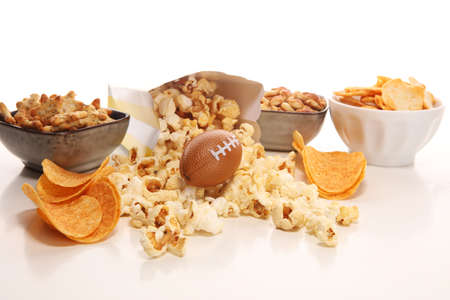 Chips, salty snacks, football on a table. Great for Bowl Game. Фото со стока