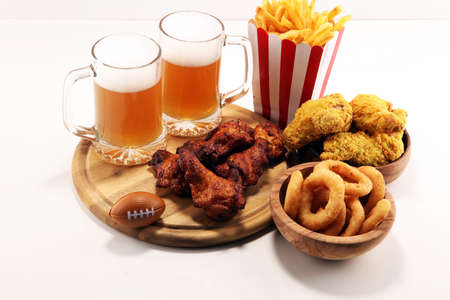 chicken wings, fries, beer and onion rings for football on a table. Great for Bowl football Game