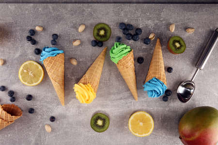 Vanilla frozen yogurt or soft ice cream in waffle cone. Different flavor ice cream with kiwi and pistachio, lemon and blueberry
