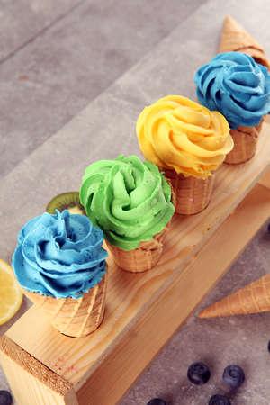 Vanilla frozen yogurt or soft ice cream in waffle cone. Diffrent flavor ice cream with kiwi and pistachio, mango and lemon, blueberry and blackberry