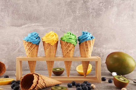 Vanilla frozen yogurt or soft ice cream in waffle cone. Diffrent flavor ice cream with kiwi and pistachio, mango and lemon, blueberry