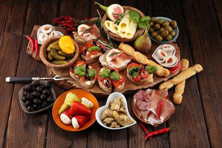 Italian antipasti wine snacks set. Cheese variety, Mediterranean olives, pickles, Prosciutto di Parma, tomatoes, artichokes on table Archivio Fotografico