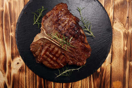 Grilled T-bone steak on stone plate. bbq grill bone steak set