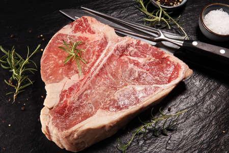 Raw T-bone steak on stone plate. bbq bone steak set