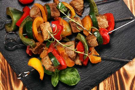 Grilled pork shish or kebab on skewers with vegetables . Food background shashlik or chicken skewers Stock Photo