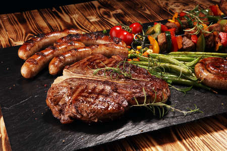 Assorted delicious grilled meat with vegetable on a barbecue with t-bone steak and sausages