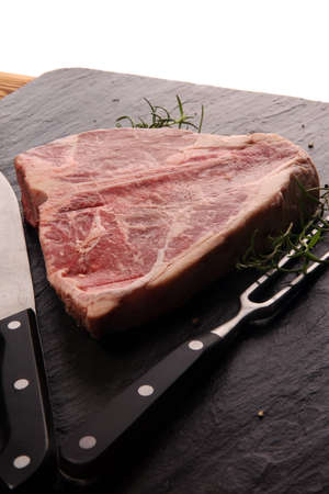 Raw T-bone steak on stone plate. bbq bone steak set