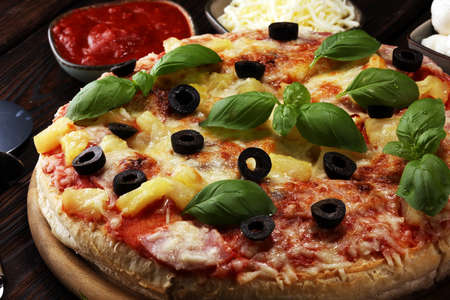 Delicious pizza with pineapple, ham slice, bacon slice, mozzarella cheese, pizza sauce on rustic background for fast food and ready to eat concept. pizza hawaii