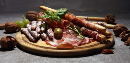 Food tray with delicious salami, coppa,  fresh sausages and herbs. Meat platter with selection on wood Stock Photo