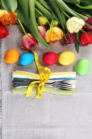 Festive table setting for Easter with fork, knife and tulip on spring