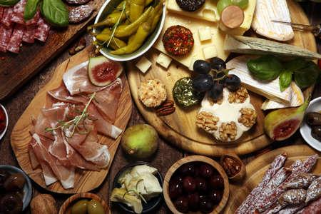 Italian antipasti wine snacks set. Cheese variety, Mediterranean olives, crudo, Prosciutto di Parma, salami and wine in glasses over wooden grunge background Фото со стока