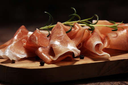 Italian prosciutto crudo or jamon with rosemary. Raw ham on wooden background