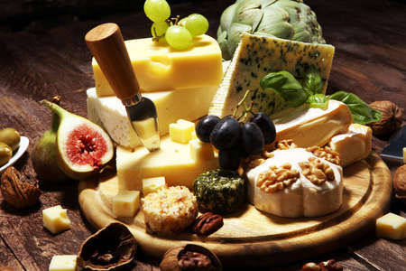 Cheese plate served with figs, various cheese on a platter on wooden table 写真素材