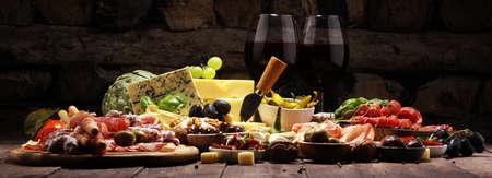 Italian antipasti wine snacks set. Cheese variety, Mediterranean olives, crudo, Prosciutto di Parma, salami and wine in glasses over wooden grunge background Reklamní fotografie