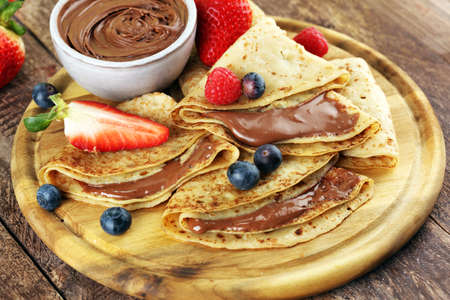 Delicious Tasty Homemade crepes with chocolate or pancakes with raspberries and blueberries on wood Foto de archivo