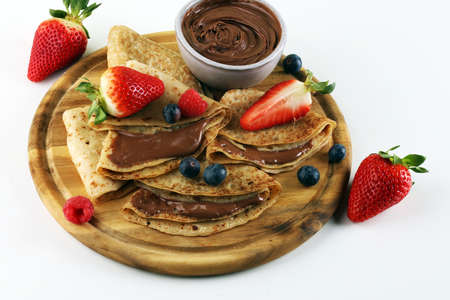 Delicious Tasty Homemade crepes with chocolate or pancakes with raspberries and blueberries on wood
