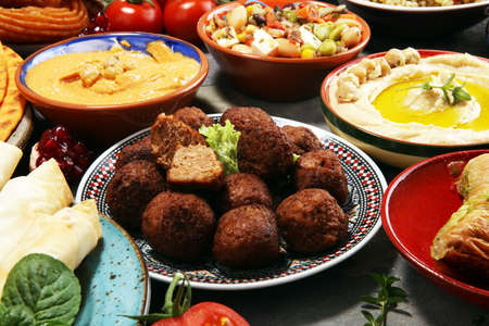 Middle eastern or arabic dishes and assorted meze, concrete rustic background. Falafel. Turkish Dessert Baklava with pistachio. Middle eastern or arabic dishes and assorted meze, concrete rustic background. Meat kebab, falafel, baba ghanoush, muhammara, hummus, tahini, kibbeh, pita. Halal food. Lebanese cuisinealal food. Lebanese cuisine