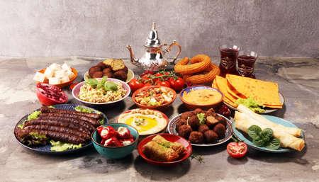 Plats du Moyen-Orient ou arabes et meze assortis, fond rustique en béton. Falafel. Dessert turc Baklava à la pistache. Brochette de viande, falafel, baba ghanoush, muhammara, houmous, tahini, kibbeh, pita. Nourriture halal. Cuisine libanaise. Cuisine libanaise Banque d'images