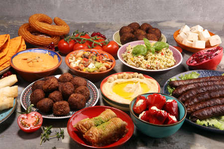Middle eastern or arabic dishes and assorted meze, concrete rustic background. Falafel. Turkish Dessert Baklava with pistachio. Meat kebab, falafel, baba ghanoush, muhammara, hummus, tahini, kibbeh, pita. Halal food. Lebanese cuisinealal food. Lebanese cuisine