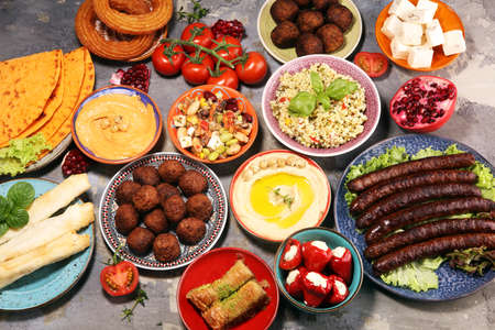Middle eastern or arabic dishes and assorted meze, concrete rustic background. Falafel. Turkish Dessert Baklava with pistachio. Meat kebab, falafel, baba ghanoush, muhammara, hummus, tahini, kibbeh, pita. Halal food. Lebanese cuisinealal food. Lebanese cuisine