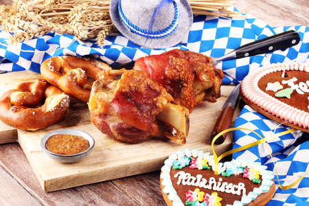 Traditional German cuisine, Schweinshaxe roasted ham hock. pretzels Bavarian specialties. Oktoberfest background