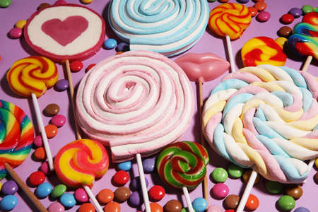 lollipop candies with jelly and sugar. colorful array of different childs sweets and treats on pink Stock Photo