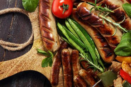 Carne alla griglia deliziosa assortita con verdure su un barbecue e shish o kebab di maiale alla griglia su spiedini con verdure. Archivio Fotografico
