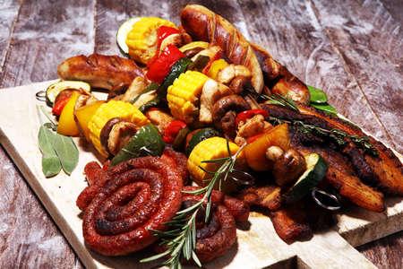 Viande et brochette grillées délicieuses assorties avec le légume et les herbes sur la table rustique