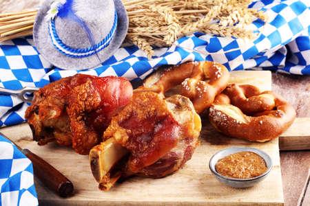 Traditionelle deutsche Küche, Schweinshaxe gebratene Schinkenhaxe. Brezeln Bayerische Spezialitäten. Oktoberfest-Hintergrund Standard-Bild