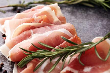 Italian prosciutto crudo or jamon with rosemary. Raw ham appetizer Фото со стока