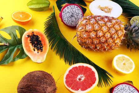 Exotic fruits and tropical palm leaves on pastel yellow background - papaya, mango, pineapple, banana, carambola, dragon fruit, lemon, orange, melon, coconut, lime. Stock Photo