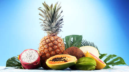 Fresh tropical Fruits on the beach with a palm leave. Assorted tropical fruits, orange,Ananas or pineapple Archivio Fotografico