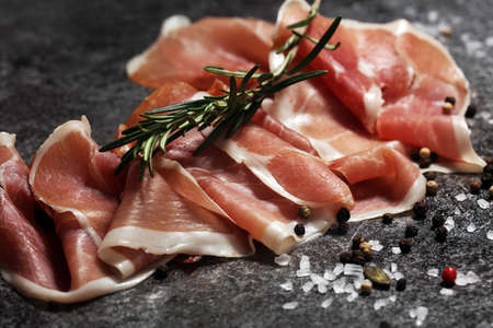 Italian prosciutto crudo or jamon with rosemary. Raw ham appetizer Standard-Bild - 120624487
