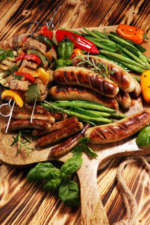 Assorted delicious grilled meat with vegetable on a barbecue and grilled pork shish or kebab on skewers with vegetables.