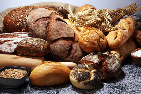 Assortment of baked bread and bread rolls on rustic table background.