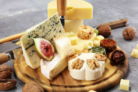 Cheese plate served with figs, various cheese on a platter on wooden table