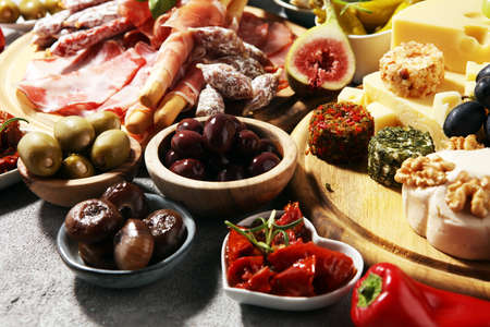 Italian antipasti wine snacks set. Cheese variety, Mediterranean olives, crudo, Prosciutto di Parma, salami and wine in glasses over wooden grunge background