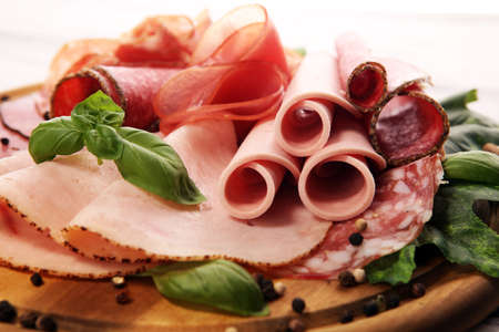 Food tray with delicious salami, pieces of sliced ham, sausage - Meat platter with selection Stock Photo