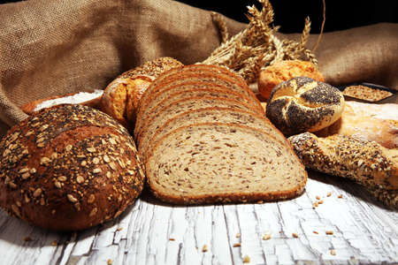 Auswahl an gebackenem Brot und Brötchen auf rustikalem Tischhintergrund.