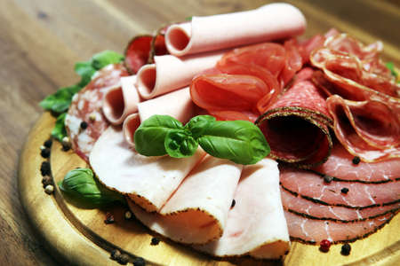Food tray with delicious salami, pieces of sliced ham, sausage - Meat platter with selection Фото со стока