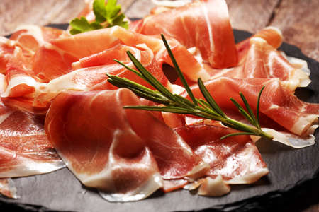 Italian prosciutto crudo or jamon with rosemary. Raw ham on wood