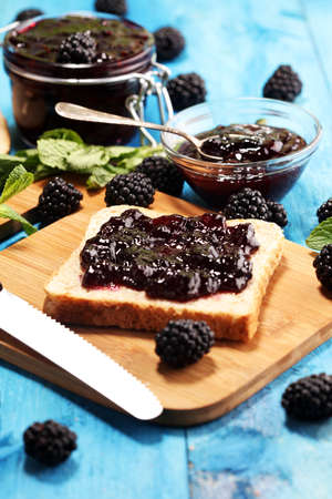 Toast bread with homemade blackberry jam or marmalade on rustic blue table served with butter for breakfast or brunch